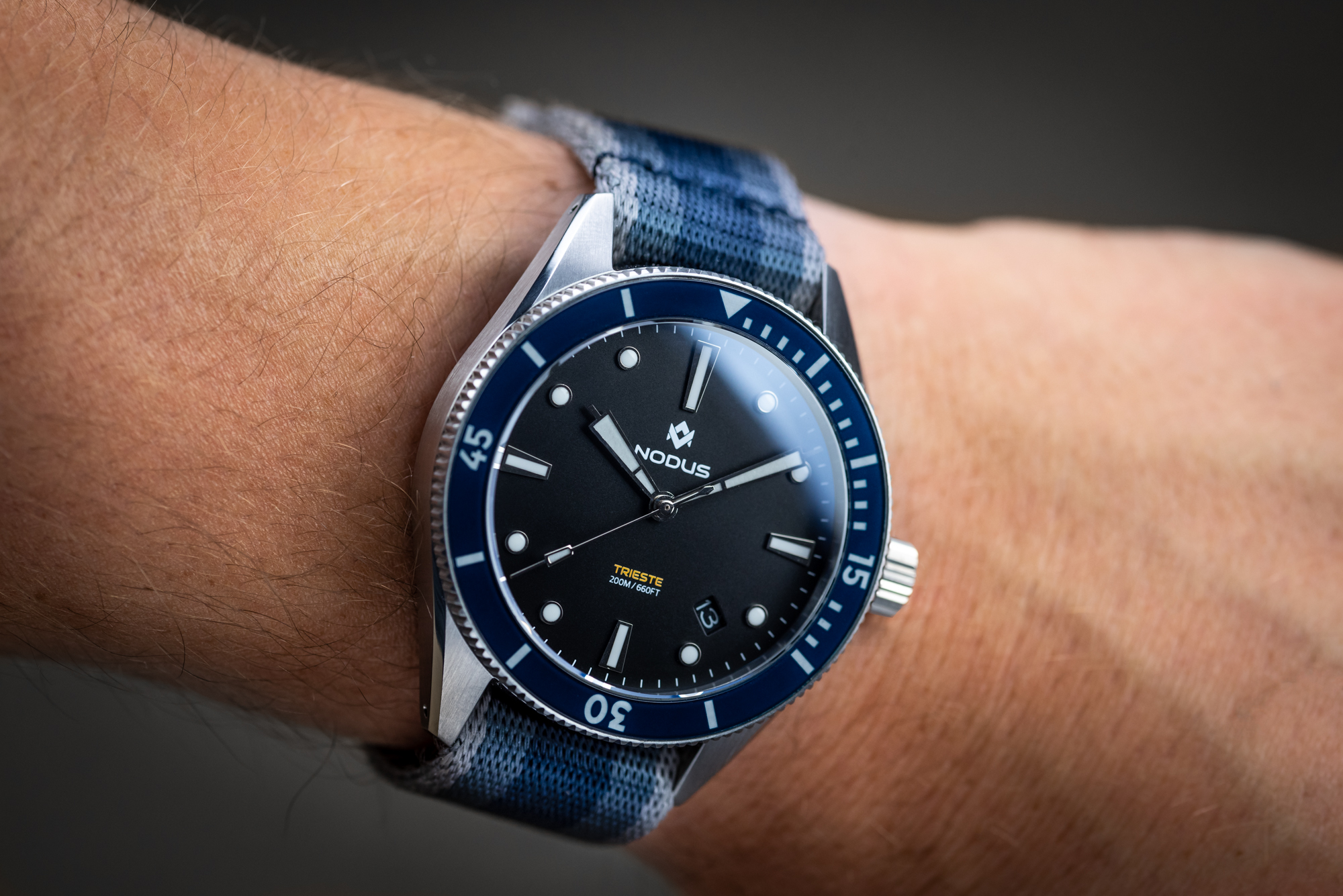 A wrist shot of the Nodus Trieste dive watch in a black dial and blue bezel. The dimensions of this watch allow it to fit almost any wrist perfectly